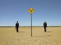 Die Geschäftsmänner, die hinter gehen, Verkehrsschild herein Wüste Stockbilder