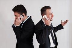 Die Geschäftsmänner, die telefonisch über einen weißen Hintergrund sprechen Lizenzfreie Stockfotos