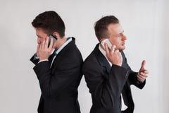 Die Geschäftsmänner, die telefonisch über einen weißen Hintergrund sprechen Lizenzfreies Stockfoto