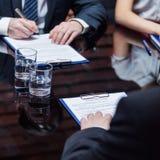 Die Geschäftsmänner, die Unterzeichnung zu den Dokumenten geben Stockfotos