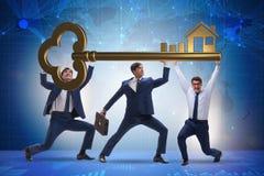 Die Geschäftsmänner, die riesigen Schlüssel im Immobilienkonzept halten Lizenzfreies Stockbild