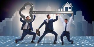 Die Geschäftsmänner, die riesigen Schlüssel im Immobilienkonzept halten Stockbilder
