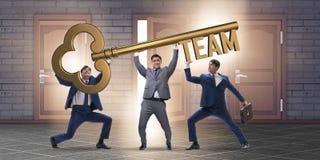 Die Geschäftsmänner, die riesigen Schlüssel im Teamkonzept halten Stockfotografie