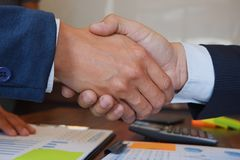 Die Geschäftsmannhändedruckberatung stimmen Abkommen zu stockbild