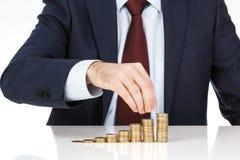 Die Geschäftsmannhand, die einen Euro stapelt, prägt in zunehmende Spalten Stockfotografie