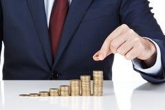 Die Geschäftsmannhand, die einen Euro stapelt, prägt in zunehmende Spalten Stockbild