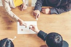 Die Geschäftsmannteamarbeit, die zwei zackige Verbindungspaare hält, verwirren Stück für die Anpassung an Ziele des Ziels, lizenzfreies stockfoto