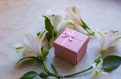 Die Geschenkbox, die mit Alstroemeria umgeben wird, blüht auf Marmoroberfläche Stockfotografie