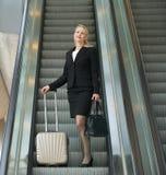 Die Geschäftsfrau, die auf Rolltreppe mit Reise steht, bauscht sich Stockfotos