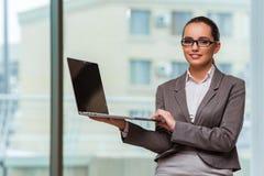 Die Geschäftsfrau mit Laptop im Geschäftskonzept Stockfotografie