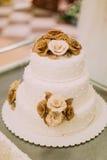 Die geschmackvolle weiße Hochzeitstorte wird mit chocolade Rosen verziert Lizenzfreie Stockfotografie