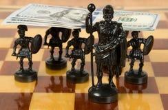 Die geschnitzten Schachfiguren, die vom Elfenbein gemacht werden, halten den amerikanischen Dollar Lizenzfreie Stockbilder