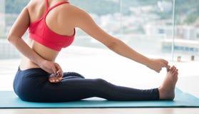 Die gesunden Frauen, die Übungskleidung tragen, spielen Yogaentspannung in janu sirsasana Lage Stockbilder