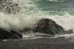 Die Gischt, ein Spritzen der Welle stieß in den Stein zusammen stockfotos