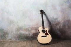 Die Gitarre steht nahe der Wand im Stil der Grunge, Musik, Musiker, Hobby, Lebensstil, Hobby Stockfotografie