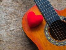 Die Gitarre und das rote Herz auf hölzernem Beschaffenheitshintergrund Liebe, Mus stockbilder