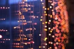 Die glänzenden Weihnachtsgirlanden auf einem hölzernen Hintergrund Lizenzfreie Stockfotos