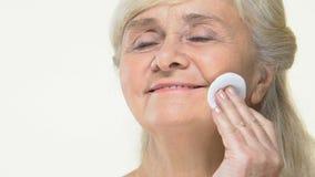 Die glückliche ältere Frau, die Gesichtswasser durch Baumwollauflage anwendet, bilden Entfernerhautpflege stock footage