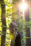 Die glückliche blonde junge Frau, die pilates tut, trainieren in einem Wald an s Lizenzfreies Stockbild