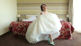 Die glückliche Braut, die auf dem Bett im Hotel sitzt, zeigt ihre schönen Schuhe stock footage
