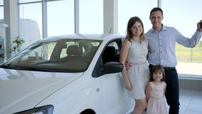 Die glückliche Familie des Porträts, die neues Auto, Familienauto, Automobilschlüssel in Kunde ` s Hand, die Leute geben Daumen k stock video