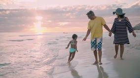 Die glückliche Familie, die auf Ozeanküste geht, silhouettiert Sonnenuntergang stock video