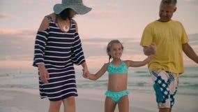 Die glückliche Familie, die auf Ozeanküste geht, silhouettiert Sonnenuntergang stock footage
