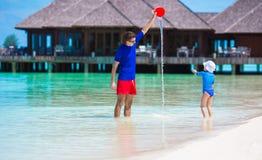 Die glückliche Familie, die mit Strand spielt, spielt auf Sommerferien Lizenzfreies Stockfoto