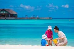 Die glückliche Familie, die mit Strand spielt, spielt auf tropischen Ferien Lizenzfreie Stockfotos