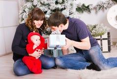 Die glückliche Familie, die Weihnachtsgeschenke hält, nähern sich Weihnachtsbaum Baby, Mutter und Vater, die Spaß zu Hause haben Stockfotos