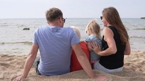 Die glückliche Familie sitzt auf dem Strand das Meer aufpassend stock video footage
