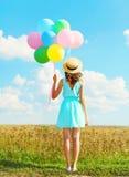 Die glückliche Frau des Schattenbildes steht mit bunten Ballonen einer Luft in einem Strohhut einen Sommertag auf Feld und blauer Stockbilder