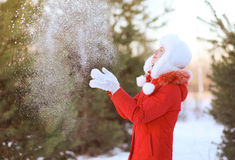Die glückliche Frau, die Spaß hat, wirft oben Schnee im Winter Stockfoto