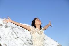 Die glückliche Frau, die tief anheben atmet, bewaffnet im Winter lizenzfreie stockfotos