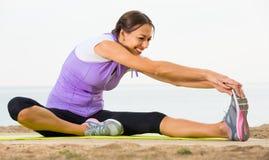 Die glückliche Frau, die Yoga tut, wirft das Sitzen auf sonnigem Strand auf Lizenzfreie Stockfotos