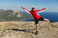 Die glückliche Frau springt auf eine Spitze eines Berges in der Sommerzeit in den Bergen den Aufstieg mit schönem felsigem und Me Lizenzfreies Stockbild