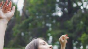 Die glückliche Frau, die tief mit Natur angeschlossen wird, glaubt Einheit, im Wald draußen zu lächeln stock footage