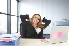 Die glückliche Geschäftsfrau, die an der BüroLaptop-Computer sitzt auf dem Schreibtisch arbeitet, entspannte sich Lizenzfreies Stockfoto