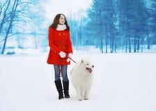 Die glückliche hübsche Frau, die mit weißem Samoyed geht, verfolgen draußen Lizenzfreie Stockfotos