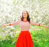 Die glückliche hübsche lächelnde Frau, die Geruch genießt, blüht in Frühling stockfotos