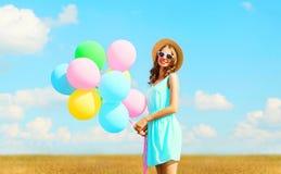 Die glückliche hübsche lächelnde junge Frau hält bunte Ballone einer Luft einen Sommertag auf einem blauen Himmel der Wiese genie Lizenzfreie Stockfotos