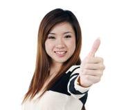 Die glückliche junge Frau, die Daumen gibt, up Zeichen Stockfoto