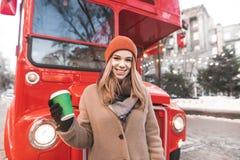 Die glückliche junge Frau, die eine Kappe und warmen Kleidungsstände auf dem Hintergrund eines roten Busses mit einem Tasse Kaffe lizenzfreies stockfoto