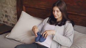 Die glückliche junge Frau spielt mit Babyschuhen gehend sie auf ihrem schwangeren Bauch und lächelndes Denken an Kind mit stock video footage
