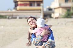 Die glückliche lächelnde arabische moslemische Mutter, die islamisches hijab trägt, umarmen ihr Baby in Ägypten
