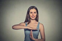 Die glückliche, lächelnde Frau, die Zeit heraus zeigt, gestikulieren mit den Händen Stockfoto