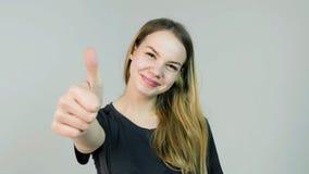 Die glückliche lächelnde schöne junge Frau, die Daumen zeigt, up Geste auf weißem Hintergrund lizenzfreie stockfotografie