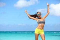 Die glückliche nette Eignungsfrau in der Sonnenbrille die Arme gewinnend, die oben v-Hand tun, unterzeichnet Lizenzfreies Stockfoto