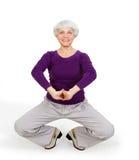 Die glückliche reizend schöne ältere Frau, die Übungen tut, beim Ausarbeiten des Spielens trägt zur Schau Stockbild