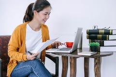 Die glückliche zufällige junge asiatische Frau, die im Haupt- oder kleinen Büro mit der Anwendung eines Laptops und des Dokuments lizenzfreie stockbilder